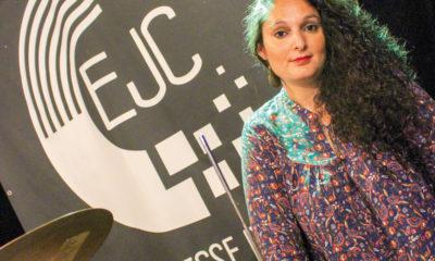 Mélissa Aït Mesghat, directrice de l'Espace Jeunesse et Culture de Soissons, pose pour la photo devant le logo de l'association.